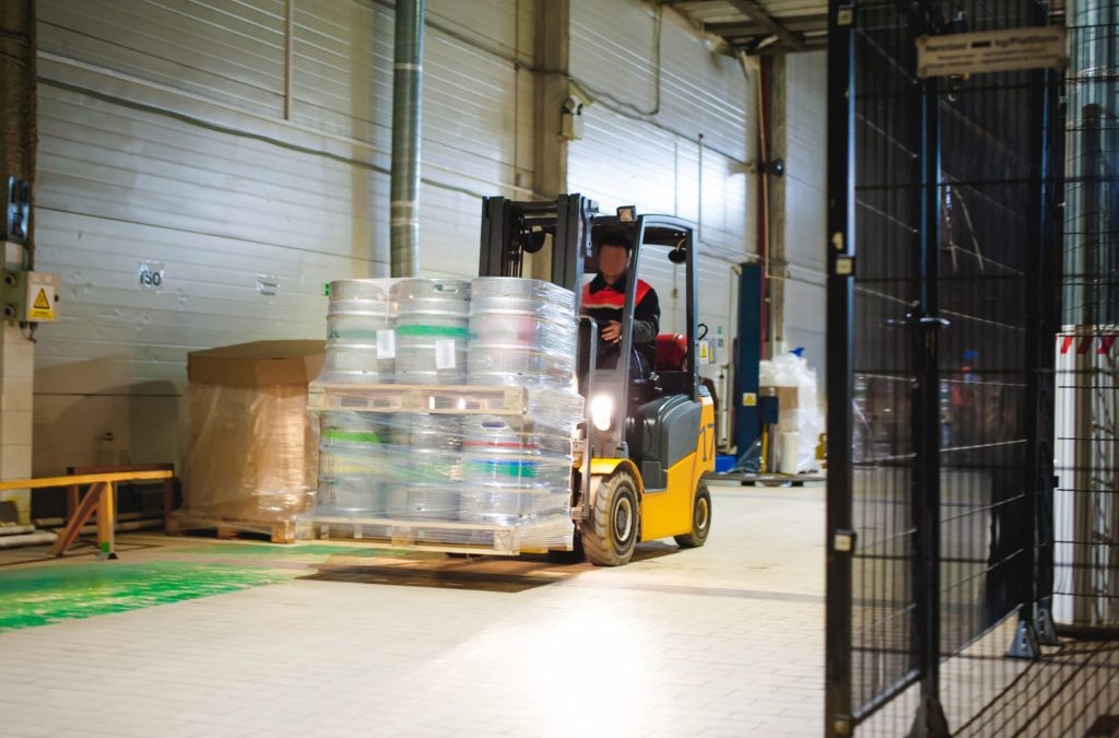 Warehouse employee in Overalls clothes, driver Reachtruck busy working on logistics Moving on loader pallets with beer kegs on line of factory for production of beer. human labor in manufacturing